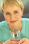 Sporty young woman holding glass of water (grainy effect)