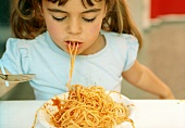 Girl eating spaghetti with tomato sauce (grainy effect)