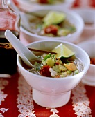 Spicy Asian soup with rice noodles & vegetable flowers in bowl