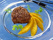 Peppered steak with mango wedges on glass plate