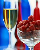 Fresh raspberries in glass bowl and a glass of champagne