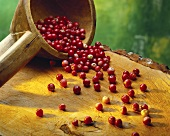 Cranberries falling out of a wooden ladle
