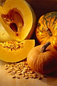 Whole pumpkins, pumpkin with piece cut and pumpkin seeds