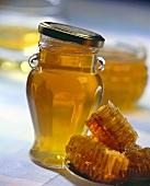 Honeycombs beside honey in screw-top jar