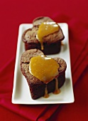 Heart-shaped chocolate cakes with caramel sauce