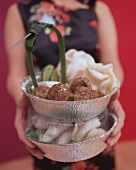Woman holding Asian style meatballs with prawn crackers