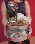 Frau hält asiatisch gewürzte Hackbällchen mit Krupuk