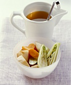 Jug of clear broth and dish of soup vegetables