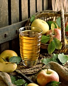 A glass of apple juice with apples as decoration