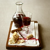 Glass of red wine with carafe, cork, corkscrew and white bread