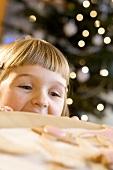 Kleines Mädchen schaut über die Tischkante auf Plätzchen