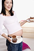 Pregnant woman, holding pieces of cake on a plate