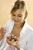 Young woman holding bowl of fruit muesli