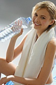 Young woman with towel round neck, holding a water bottle