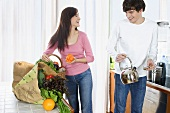 Young couple standing in kitchen (with shopping)