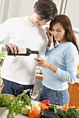 Young couple standing in kitchen, man pouring wine