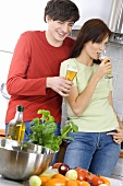 Young couple standing in kitchen, with beer glasses