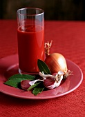 Tomato sauce in a glass on table with ingredients