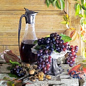 Still life with red wine grapes and a carafe of red wine