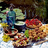 Buffet with kebabs and cakes by garden pond