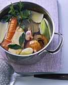 Clear meat broth with vegetables in pan