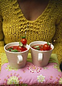 Woman carrying two cups of tomato soup on cushion