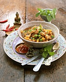 Cauliflower and mango curry with peas in small bowl