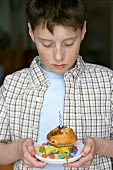 Boy holding muffin with burning candle