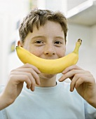 Boy holding banana in front of his face