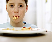 Junge mit drei Pommes im Mund