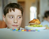 Boy looking at muffin with burning candle