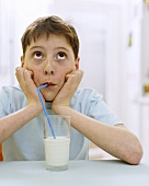 Boy drinking milk through a straw