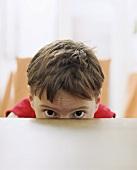 Boy hiding behind table