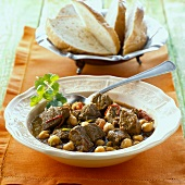 Lamb and chick-pea stew with a bread basket (India)