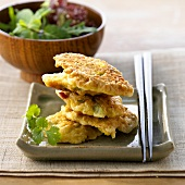 Sweetcorn cakes in a pile with salad accompaniment