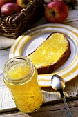 Apple & ginger jelly in jar and on a slice of bread & butter