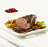 Roast beef, slices carved, and a bowl of cherries