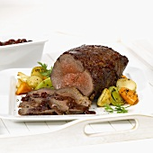 Barbecued roast beef, slices carved, with vegetables