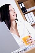 Junge Frau sitzt im Büro mit einem Glas Orangensaft