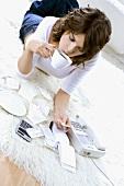 Young woman lying on floor, drinking tea & doing paperwork