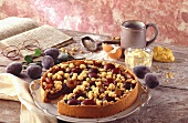 Plum cake with cookery book and baking ingredients