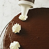 Decorating chocolate cake with cream topping