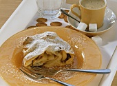Piece of Viennese apple strudel with icing sugar, with coffee