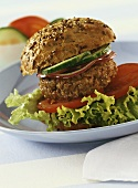 Granary roll with burger, tomatoes, cucumber and lettuce