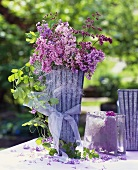 Lilac with trailing foliage in tall vase