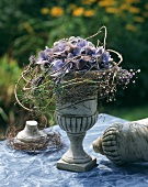 Goblet with blue hydrangea and trailing foliage