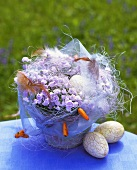 Easter arrangement of bluebells, feathers and eggs
