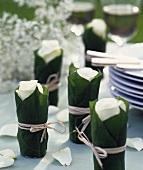 Rosenblüten in mit Blättern umwickelten Gläschen