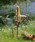 Garden tools hanging up on a stick on large lawn