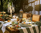 Table with autumnal decorations, tableware & candlestick